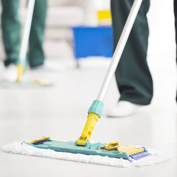 Person holding and cleaning floor mop with Dalcon Higiene product