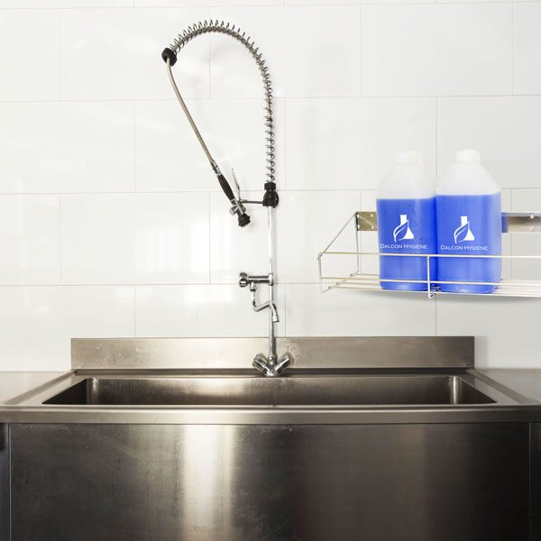 Commercial kitchen sink with storaging chemicals in a wire rack